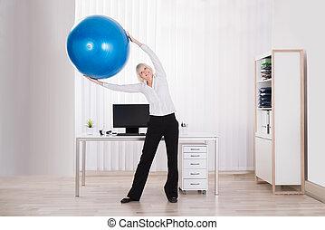 businesswoman, stretching, haar, armen, in, kantoor