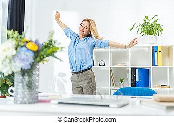 businesswoman, stretching, in, moderne, kantoor