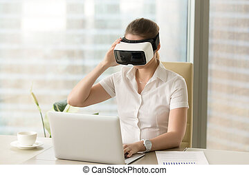 Businesswoman synchronizes VR headset with laptop