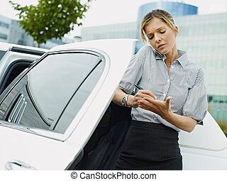 Businesswoman Takes Notes On Palm Of Hand During Phone Call