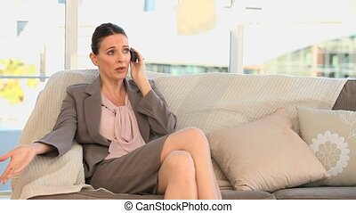 Businesswoman taking a phone call on a sofa