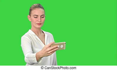 Businesswoman taking funny selfie with phone on a Green Screen, Chroma Key.