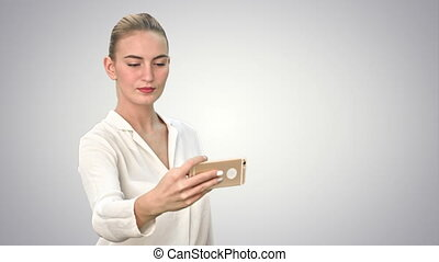 Businesswoman taking funny selfie with phone on white background.