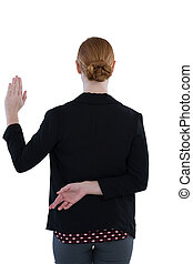 Businesswoman taking oath with fingers crossed