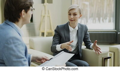 Businesswoman talking and duscussing company finance information with male business partner sitting on armchair in modern office