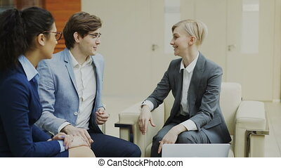 Businesswoman talking and duscussing future contract with business partners sitting on couch in modern office center