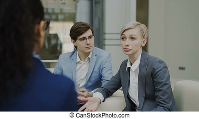 Businesswoman talking and duscussing future deal with business partners sitting on couch in modern office center
