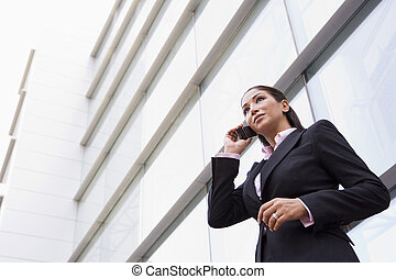 Businesswoman talking on cell phone outside