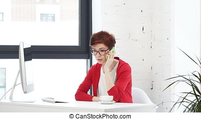 Businesswoman talking on cell telephone while sitting front of computer screen in office.