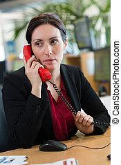 businesswoman talking on landline phone in office
