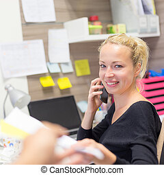 Business and entrepreneurship consept. Beautiful blonde business woman talking on mobile phone in colorful modern creative working environment accepting papers. Female multi tasking.