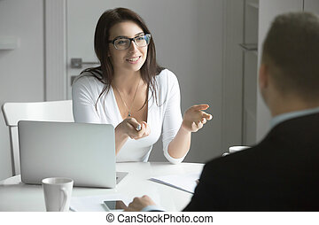 Businesswoman talking to a man at the desk