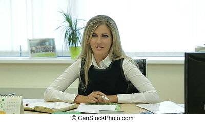 Businesswoman talking to camera on table in office