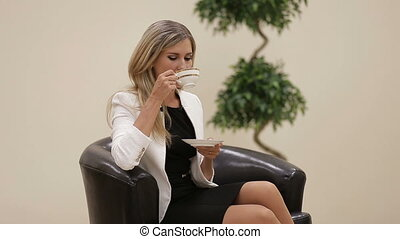 Businesswoman talking to camera with a cup of coffee