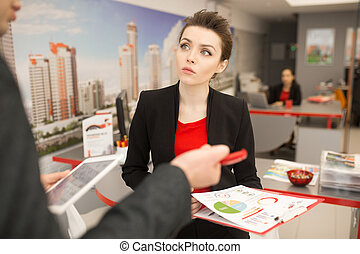 Businesswoman Talking to Colleague in Agency