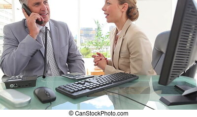Businesswoman talking to her colleague while he is on the phone