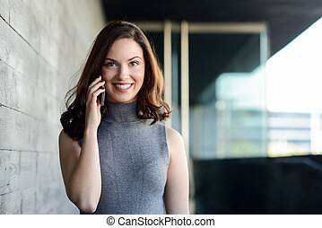 Businesswoman talking with a smartphone in an office building