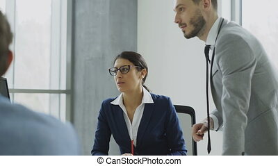Businesswoman talking with male and female colleagues sitting at the table in modern office