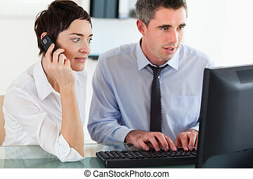 Businesswoman telephoning while her colleague is using a computer in an office