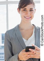 Businesswoman texting and smiling at camera
