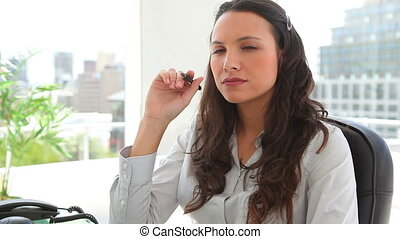 Businesswoman thinking while holding a pen