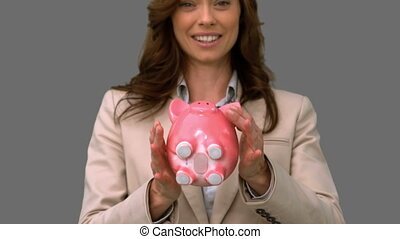 Businesswoman throwing a piggy bank on grey screen in slow...