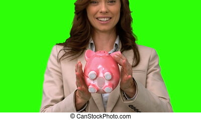 Businesswoman throwing a piggy bank on green screen in slow...