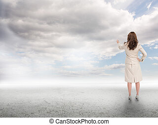 Businesswoman touching at the sky