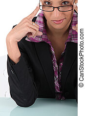 Businesswoman touching the frame of her glasses