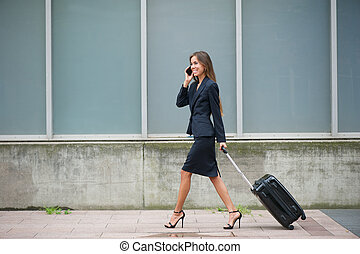 Businesswoman traveling with suitcase