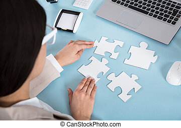 Businesswoman Trying To Join The Jigsaw Puzzle Pieces