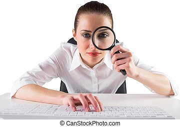 Businesswoman typing and looking through magnifying glass on...
