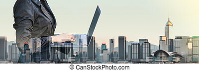 Businesswoman typing on laptop computer double exposure with blur cityscape building in morning, Business banner size, Technology communication concept