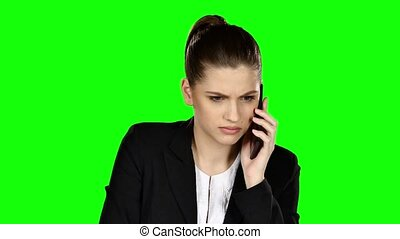 Businesswoman under stress speaking at the phone. Green screen