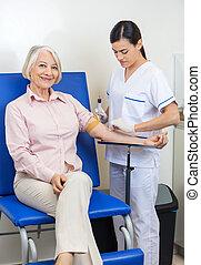 Businesswoman Undergoing Blood Test In Clinic