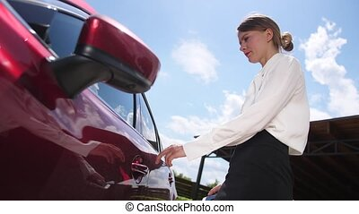 Close-up of attractive female in business clothes using modern technology to unlock car doors holding cellphone with special application. Formally dressed businesswoman opening door and getting in car