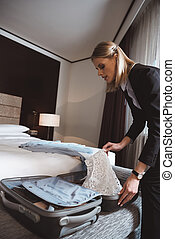 businesswoman unpacking suitcase in hotel room
