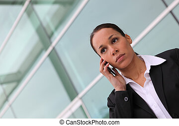Businesswoman using a cellphone outside an office block