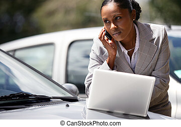 Businesswoman using a laptop and mobile phone by her car