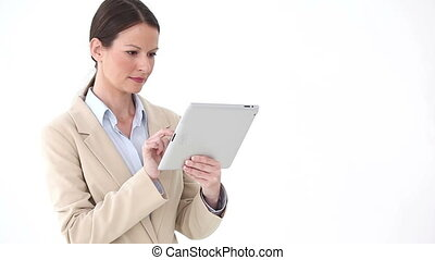 Businesswoman using an eBook while standing against white...
