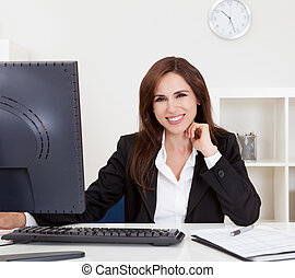 Portrait of a beautiful young businesswoman at desk using computer