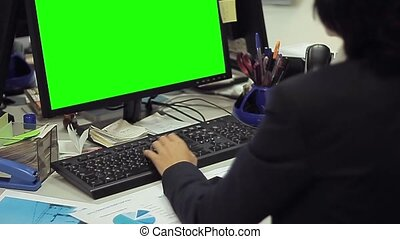 woman using computer with green screen