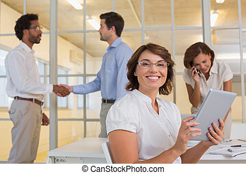 Businesswoman using digital table with colleagues at office