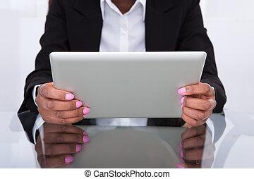 Businesswoman Using Digital Tablet At Desk