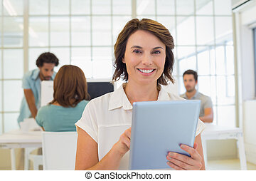 Businesswoman using digital tablet with colleagues in meeting