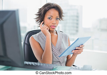 Businesswoman using her digital tablet at desk