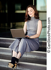 Businesswoman using her laptop computer in a modern office building