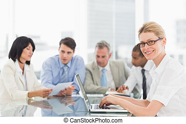 Businesswoman using her laptop during a meeting looking at camera in the office