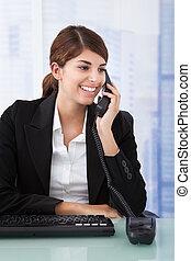 Businesswoman Using Landline Phone In Office - Portrait of ...