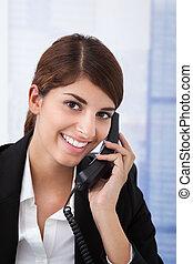 Businesswoman Using Landline Phone In Office